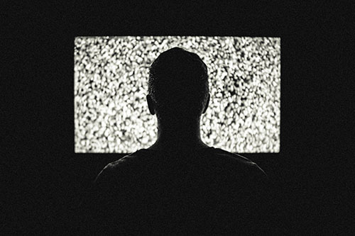 guy in front of bright tv